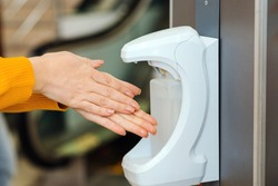 Washing hands using automatic sanitizer dispenser. Automatic sanitizer dispenser at supermarket. Coronavirus prevention. Coronavirus. Disinfectant in a shopping mall during the coronavirus epidemic.