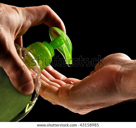 washing hands with liquid soap isolated on black - stock photo