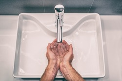 Washing hands with soap at work bathroom sink man hand care hygiene for coronavirus outbreak prevention. Corona Virus pandemic precaution by washing hands frequently for 20 seconds.
