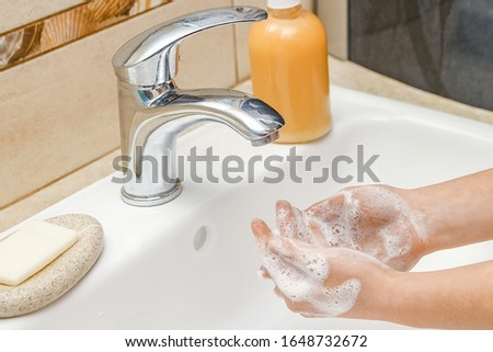 Washing hands with soap under the faucet with water