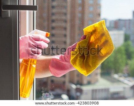 washing home window - washer washes window glass with detergent in apartment house #423803908