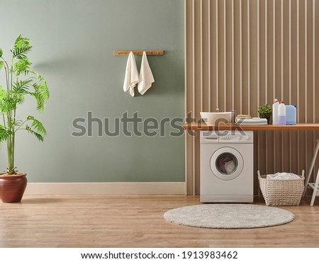 Washing machine in the laundry room style, interior concept, dirty clothes decor coffee table with vase of plant. Wooden bench, sink and towel.