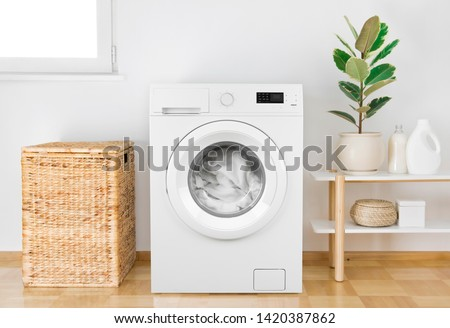 Washing machine with clothes in modern bathroom interior