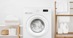 Washing machine with laundry and shelves on white wall background