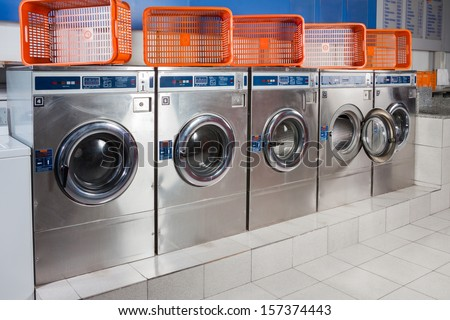 Washing Machines And Empty Baskets In A Row At Laundromat