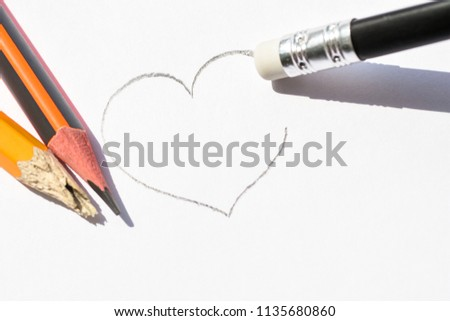 Washing on pencil erases the painted heart. Simple pencils symbolize ruined love #1135680860