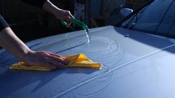washing the hood of the car in metallic gray color using a rubber hose with water and a professional cloth for cleaning car surfaces, water spreading along the body of the car during washing