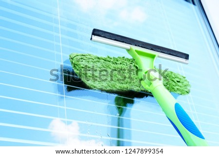 Washing the window with a special brush. Glass with sky reflection. Clean, cleaned. Jalousie. #1247899354