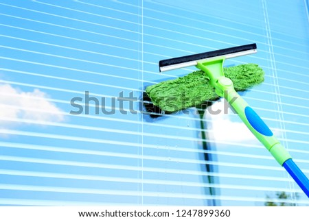 Washing the window with a special brush. Glass with sky reflection. Clean, cleaned. Jalousie. #1247899360