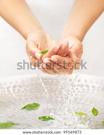 Washing women's hands with splashing and drops over the sink with water and green leaves