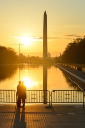 Washington D.C. - A couple enjoy sunrise at Lincoln Memorial with silhouettes of Capitol Building and Washington Monument