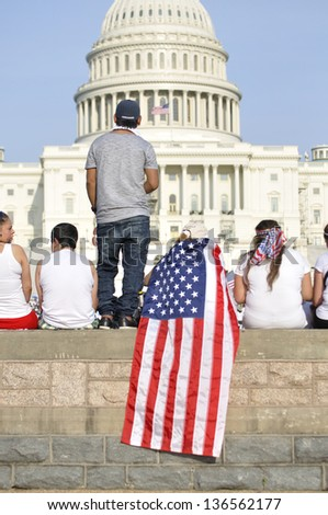 WASHINGTON D.C. - APRIL 10: Demonstrators show their American patriotism in front of the capitol during a demonstration for immigration reform in Washington D.C. on April 10, 2013.