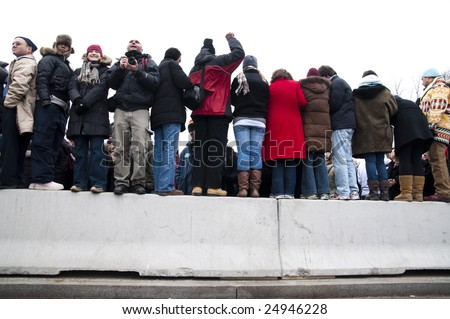 WASHINGTON, DC - JAN. 18: People  perch on a wall to watch the celebration of the 2009 inauguration of President Barack Obama