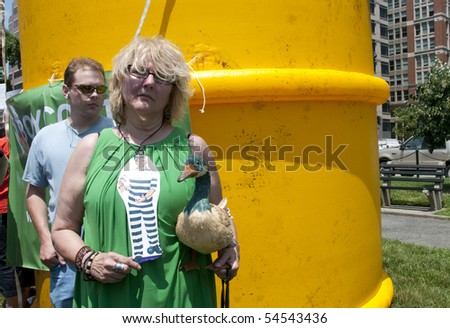 WASHINGTON, DC - June 4: Female demonstrator holds stuffed duck in front of giant inflatable oil barrel in protest against BP oil spill, June 4, 2010 in Washington, DC