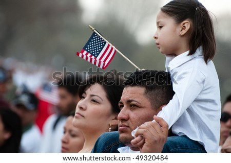 WASHINGTON, DC - MARCH 21: A girl and her father stand with some 200,000 immigrants' rights activists flood the National Mall  to demand comprehensive immigration reform on March 21, 2010 in Washington DC.