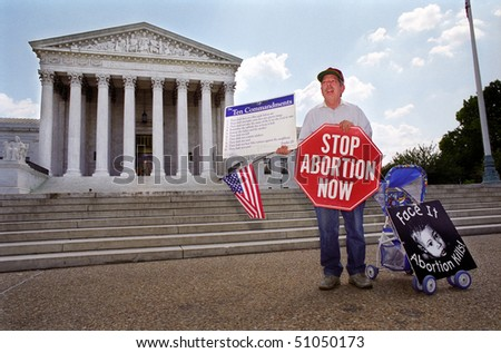 WASHINGTON, DC - MAY 14: An anti-abortion protester holds a stop sign and the Ten Commandments on the sidewalk in front of the U.S. Supreme Court on May 14, 2001 in Washington, D.C. - stock photo