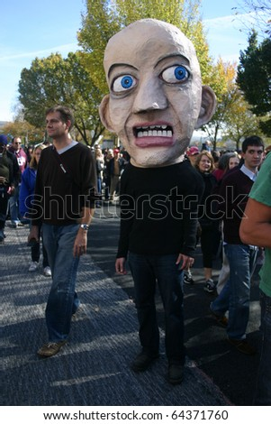 WASHINGTON, DC - OCT 30: A man with a fear-based head puppet walks among the crowd at the Stewart/Colbert Rally to Restore Sanity and/or Fear, Oct. 30, 2010 on the National Mall in Washington, DC.