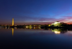 Washington DC panorama around Tidal Basin at dawn during cherry blossom in spring. Urban skyline with Thomas Jefferson Memorial and Washington Monument in US capital.