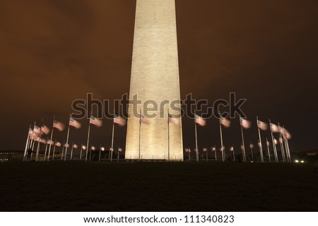 Washington Monument at night with American flags flying at the base