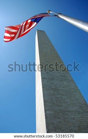Washington Monument in Washington DC with flapping american flag on a flagpole