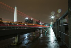Washington Monument Lit Up at Night in the Rain with Light Trails from Cars. The photo was taken from the Tidal Basin Bridge, showing the reflection of the lights on the sidewalk and pavement.