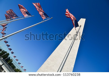 Washington Monument with waving United States flags on flagpoles - Washington DC United States