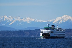 Washington State Ferry cruises in front of Olympic Mountains on approach to Seattle
