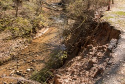 Washout and pavement collapse into the creek