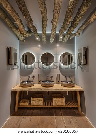 Washroom in a modern style with gray wall and a parquet in the cafe. There are hanging logs with lamps, mirrors with backlight, wooden table with sinks and baskets, soap dispensers, hand dryers. #628188857