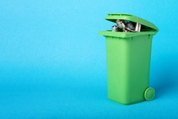 Waste batteries in a plastic container. Waste recycling. Environmental concept. Basket with batteries on a blue background.