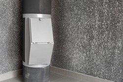Waste disposal container installed on the floor of a multi-storey building on the grey background. Cleaning and maintenance concept trash and linen and chute systems. Copy space.