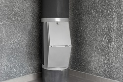 Waste disposal container installed on the floor of a multi-storey building on the grey background. Cleaning and maintenance concept trash and linen and chute systems.