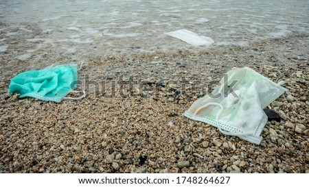 Waste during COVID-19. Discarded to ocean coronavirus single-use face masks. Environmental and coast plastic pollution. Trash in the beach threatening the health of oceans.