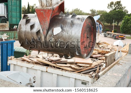 Waste garbage compactor working on a dumpster bin in an outdoors municipal public dumb collector