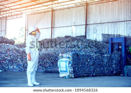 Waste processing plant. Technological process plastic bottles at the factory for processing and recycling. The worker recycling factory,engineers is out of focus or blurred.