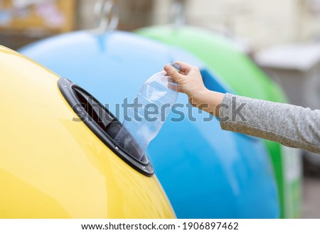 Waste Recycling Concept. Unrecognizable lady throwing plastic bottle into yellow recycle bin container outdoors, sorting garbage, enjoying zero waste living, cropped image with selective focus Foto stock ©