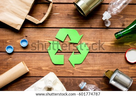 waste recycling eco symbol with garbage disposal on wooden table background top view