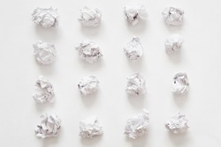 Waste recycling. Flat lay of crumpled paper ball rows on white surface. Abstract background.