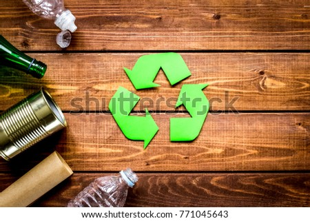 waste recycling symbol with garbage on wooden background top vie
