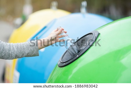 Waste Sorting And Recycling Concept. Unrecognizable female throwing empty glass bottle into green recycle bin garbage container outdoors, caring about environment, cropped image with selective focus Foto stock ©