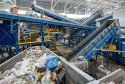 Waste sorting plant. Many different conveyors and bins. conveyors filled with various household waste.