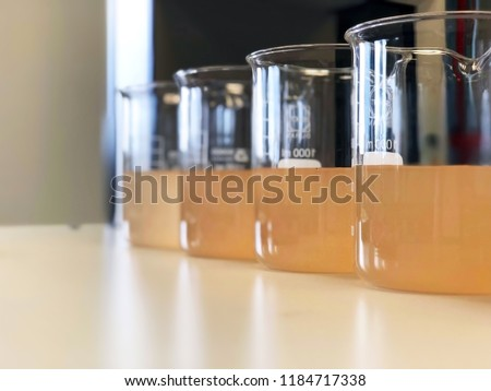 Waste water sample in beakers coagulation and flocculation method with Ferric chlorine and using Jar test for forming precipitation and reduced turbidity calibration range. Use for science background.