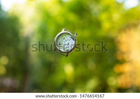 wasted time concept graphic design photography of vintage hand clock floating in air on unfocused green natural background, wallpaper pattern art picture with empty space for copy or text