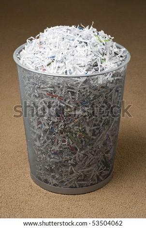 wastepaper basket filled with shredded paper on a carpet.