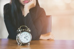 wasting time concept with Asian business woman feeling tired and bored waiting for someone coming late at work and looking at alarm clock on desk