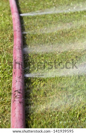 wasting water - water leaking from a hole in a hose
