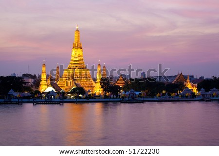 Wat Arun glowing in the pink twilight by Chao Phraya River, Bangkok, Thailand