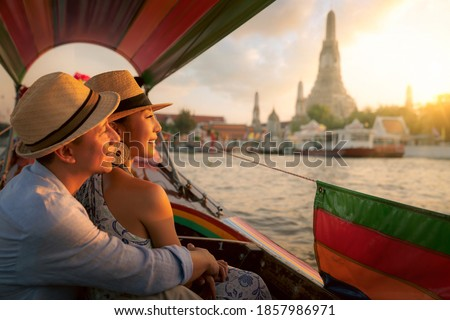 Wat Arun Ratchawararam temple. Couple traveller with boat in the Arun temple, landmark thailand tourist spot, Bangkok city, Thailand