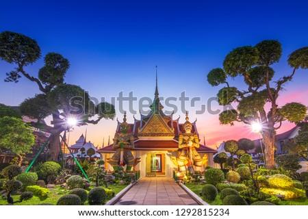 Wat Arun Temple at sunset in bangkok Thailand. Giants front of the church at Wat Arun. Wat Arun is a Buddhist temple in Bangkok Yai district of Bangkok, Thailand #1292815234