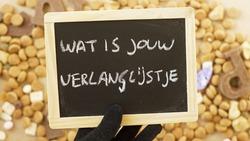 Wat is your present list written in Dutch on a chalkboard holding by Pete